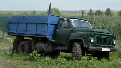 The old car is a truck. It stands in a village on the roadside with a blue body.