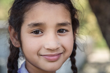 Portrait of smiling elementary Indian/Asian school girl looking at camera.