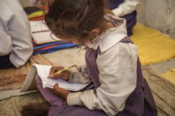 Poor Indian village school girl sitting on floor and doing her school assignment.