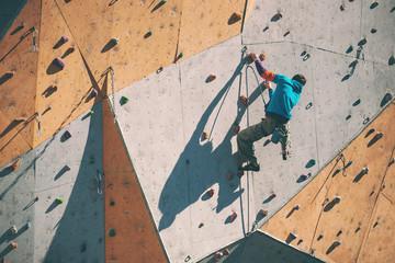 The climber climbs on an artificial relief.