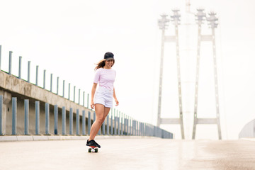 Young Beautiful Blonde Girl Riding Bright Skateboard on the Bridge