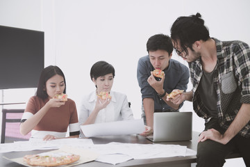 Asian people eating pizza together during lunch break.