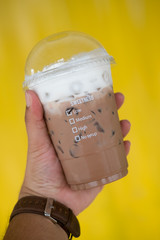 Hand with plastic glass of iced coffee