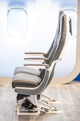 close-up of passenger aircraft seats bolted to wooden floor
