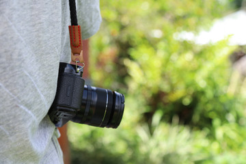 Closeup of a black camera hanging on man's shoulder with natural background in sunny day.