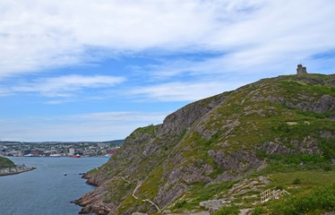 looking along side the slope from the hiking path on the bottom of Signal Hill covered with lush green grass towards  St John's harbour;  Newfoundland Canada