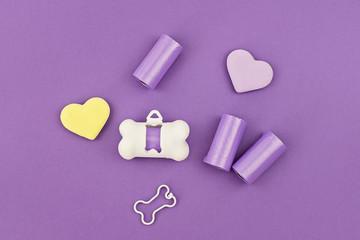 Pet dog waste poop bag dispensers and holders, bags for poop and white holder dispenser on violet background, flat lay