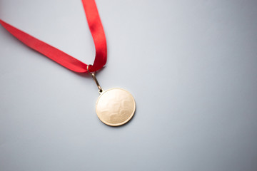 gold medal on a red ribbon on a blue background
