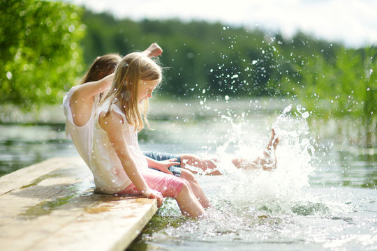 Two cute little girls sitting on a wooden platform by the river or lake dipping their feet in the water on warm summer day