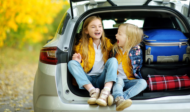Two adorable girls sitting in a car trunk before going on vacations with their parents. Two kids looking forward for a road trip or travel. Autumn break at school.