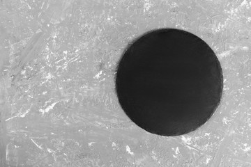 Empty Slate round plate on table. black slate dish on stone background. copy space