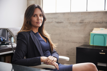 Mixed race woman sitting at desk in office turning to camera