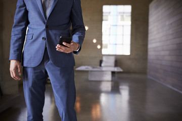 Mid section of man in blue suit using smartphone