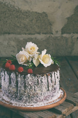 Gluten-free and dairy-free cake decorated with white roses and coconut: chocolate-nut biscuit, berry mousse, custard on almond milk and chocolate glaze. Healthy dietary baking. Vegetarian food.