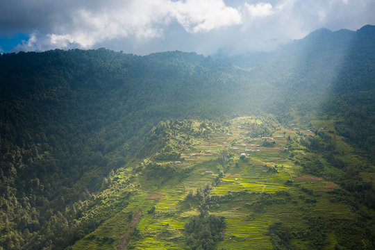 Terraced fields on a Himalayan hillside with rays of sunlight streaming down lighting up the village.