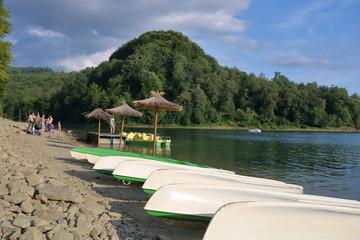 Jezioro Solińskie, Polska, na brzegu leżą, do gory dnem, kajaki, kilka trzcinowych parasoli plażowych, ludzie w strojach kąpielowych, rowerki wodne przy pomoście, zalesione wzgórze na przecownym brzeg