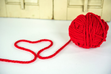ball of red yarn with heart design on white