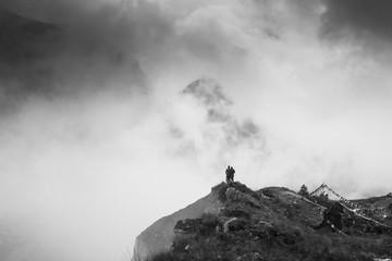 A couple standing on a ridge looking into the Annapurna moraine through the fog and clouds. Trekking the Annapurna Sanctuary to ABC in the clouds.