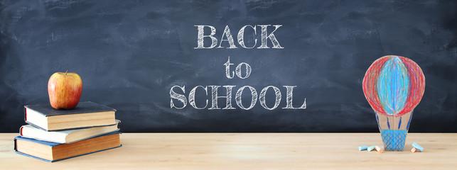 Back to school concept. cardboard handmade hot air balloon over classroom blackboard background.