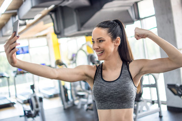 Sporty woman taking a selfie with a smart phone while showing her arm muscle at gym