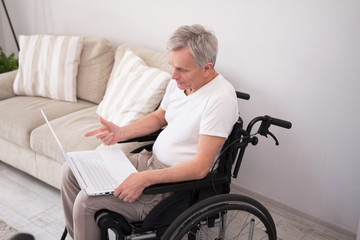 Man in wheelchair working with computer. Senior disabled man sitting in wheelchair in his living room and doing some work on his white laptop.