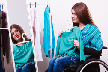 handicapped girl on wheelchair choosing clothes