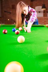 Young fashionable girl playing billiard.