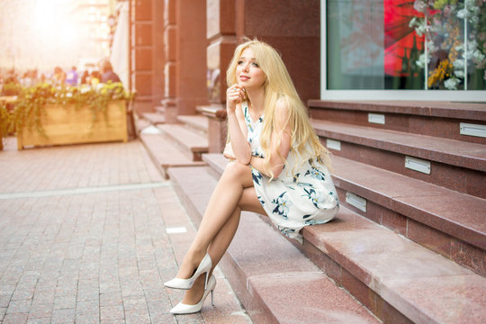Attractive blonde young woman wearing dress and high heels sitting on stairs on city street.