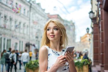 Beautiful blonde girl using smart phone on the city street.
