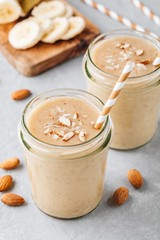 Banana almond smoothie with cinnamon and oat flakes and coconut milk in glass jars