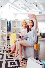Family selfie. Modern mother and daughter wearing bright sunglasses making selfie while sitting in showroom