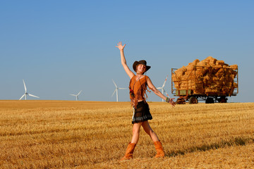 A young woman dressed as a cowgirl stands in a farmers  crop field at sunset and admires the windmills turning in  the distance.