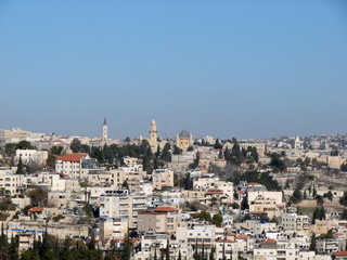 Panorama of the streets, buildings and temples of the city of Jerusalem from the height of the bird's eye on the background of a clean blue sky.