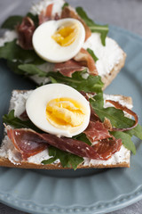 Sandwiches with whole grain bread, homemade cheese, arugula, ham and egg. Healthy snack.