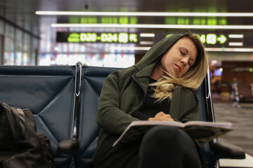 Woman transit traveller sleeping at the airport, waiting for a flight