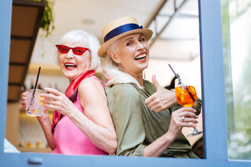 Alcoholic drinks. Positive stylish women holding glasses with cocktails while meeting in the cafe