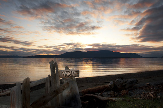 View of Orcas Island with a Private Beach Sign. Sunset over Orcas Island in the San Juan Islands archipelago with a warning about this being a private beach. Taken from Lummi Island, Washington.