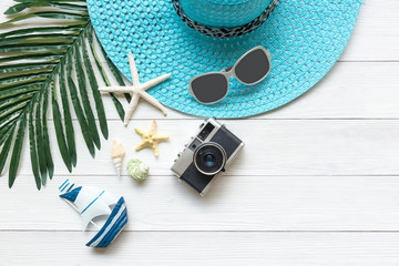Summer Fashion,  camera, starfish, sunblock, sun glasses, hat. Travel and vacations in the holiday, wood white background. Summer Concept.