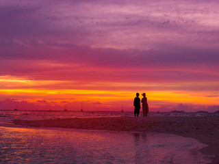 Silhouette of asian couple standing on the beach in sunset time with twilight sky at the sea for romantic honeymoon or vacations holiday concept.
