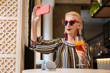 Nice photo. Pleasant fashionable woman holding a cocktail while taking selfies