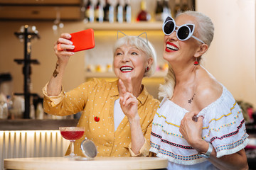 Happy moments. Delighted aged woman showing V sign while taking a selfie together with her friend