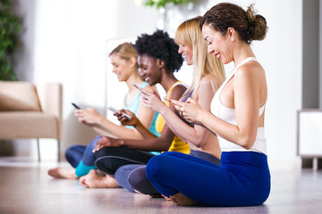 Pretty young sporty women using mobile phone after yoga session at home.