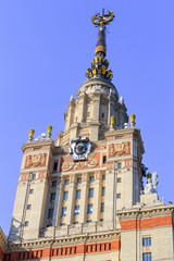Building of Lomonosov Moscow State University (MSU) with national emblem of USSR and star on the spire against blue sky