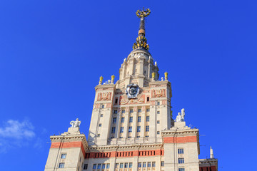 Building of Lomonosov Moscow State University (MSU) with national emblem of USSR and star on the spire in sunny summer evening