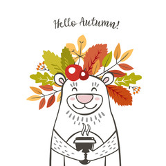 a cute bear with a wreath of autumn leaves and berries on his head with the inscription hello autumn and the cup of coffee latte