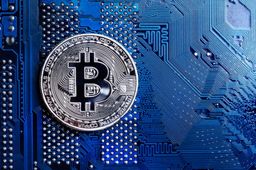 Silver bitcoin digital currency on blue circuit board. Bitcoin cryptocurrency security and mining concept. futuristic digital money, technology worldwide network concept.