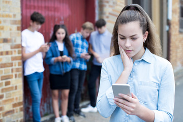 Worried Teenage Girl Being Bullied By Text Message