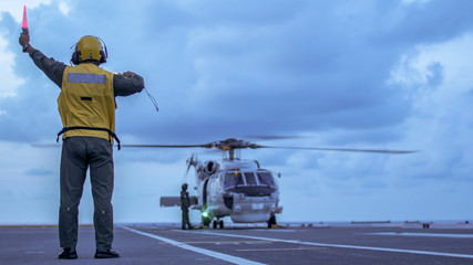 Signal man give a signal to anti-submarine warfare helicopter on the aviation deck of aircraft carrier.