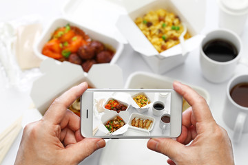 taking a photo of chinese take out food with smartphone