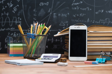 School books and stationery on a wood and a chalkboard background